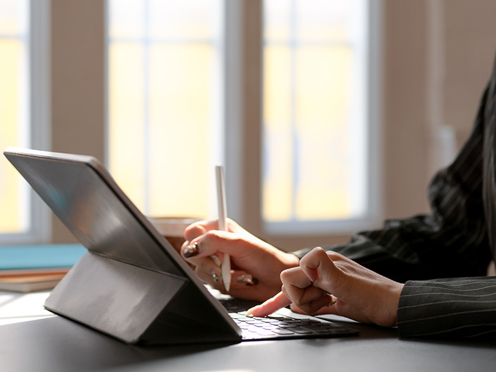 Cropped shot of female working on digital tablet with stylus and other office supplies on black desk in comfortable workplace