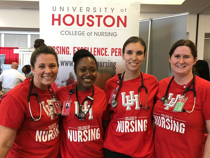 Nursing students in from of College of Nursing banner