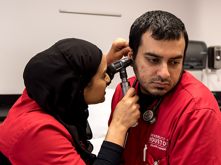 Student doing hearing check on another student