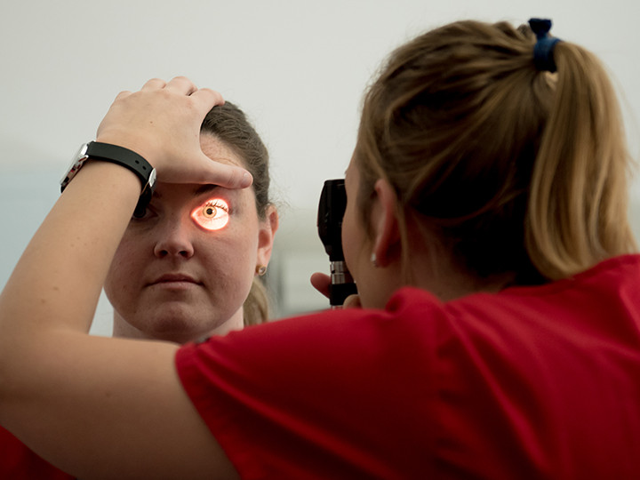 Nursing student examining eye of another student
