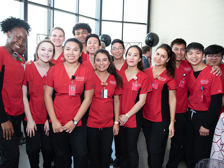Group of nursing students in red scrubs
