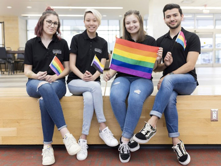 Students sitting with LGBTQ identity flags