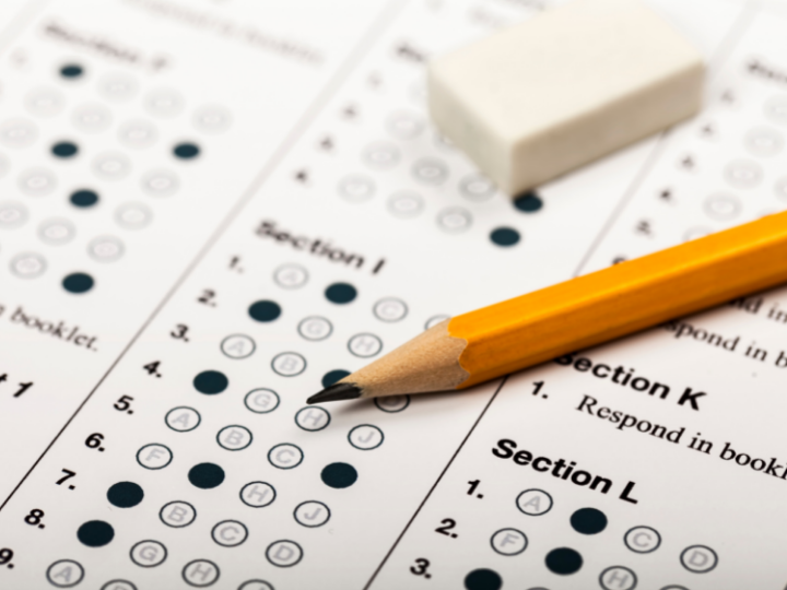 A zoomed in photo of a filled in scantron with a sharpened yellow pencil and a white eraser