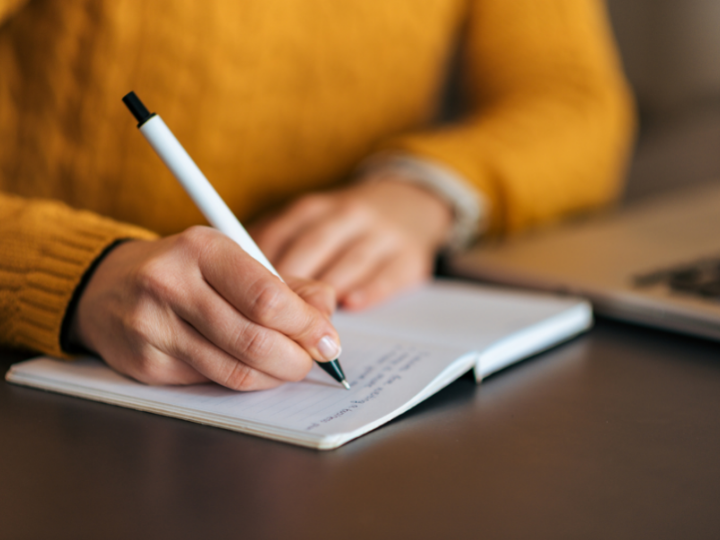 A zoomed in photo of a person is a bright yellow sweater writing with a white pen on an open notebook at a wooden desk