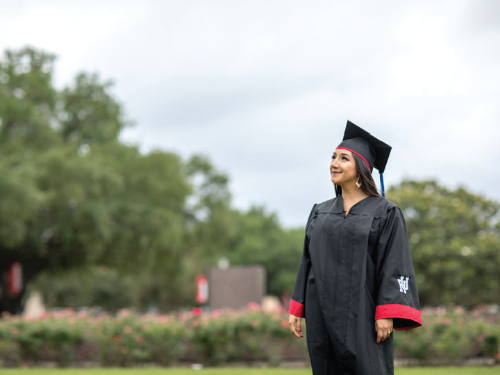 Latina student in her graduation robes looks up to the sky