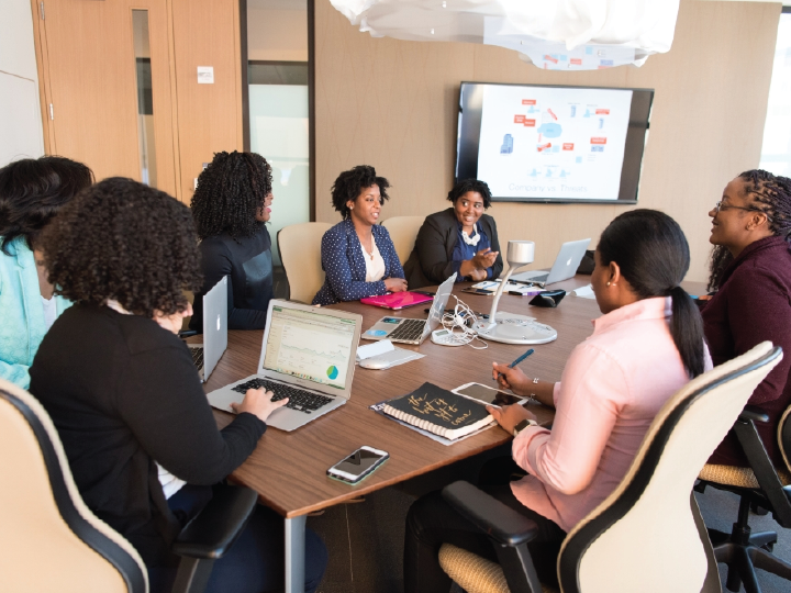 Seven Black women sit around a conference table smiling and talking