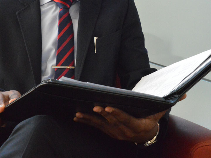 Zoomed in image of a person in a suit, light blue shirt, striped tie, and tie bar holding a black padfolio looking at paperwork insie