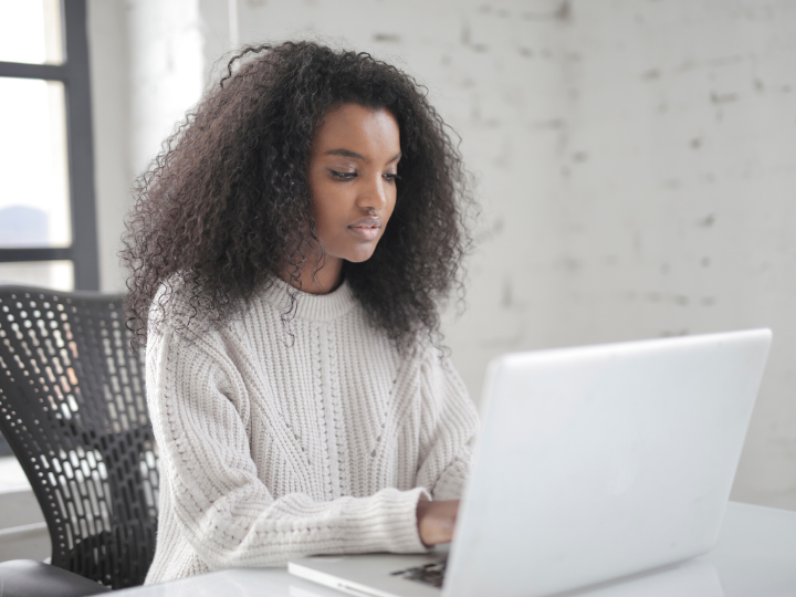 Feminine presenting person in a white sweater at a white laptop engaged with the screen and typing
